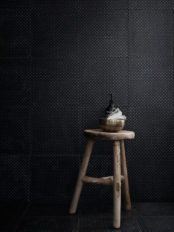 bathroom-with-black-textured-tiles.-raw-wooden-stool.